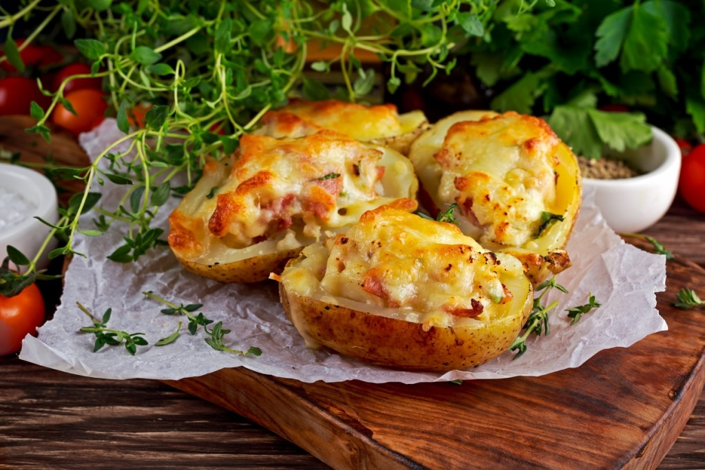 Hot Baked stuffed Potato with cheese, bacon, parsley on wooden