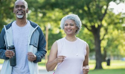 Senior adult African American couple are smiling and jogging together in public park on sunny day. Husband and wife are wearing athletic clothing.