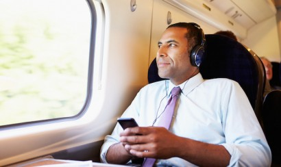 Businessman Relaxing On Train Listening To Music