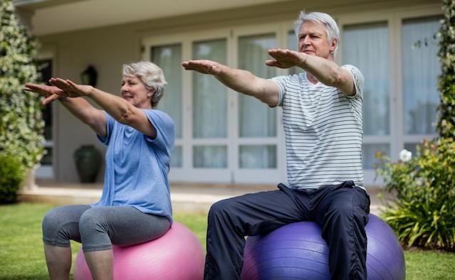 Senior couple exercising on fitness ball