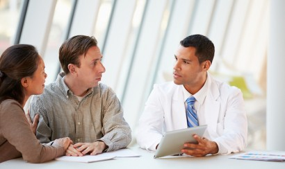 A doctor using a tablet computer in a patient's discussion