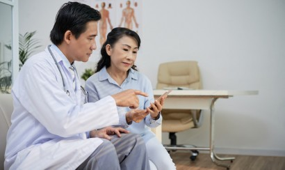 Doctor and patient look at smartphone