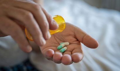 A patient pouring pills into their hands