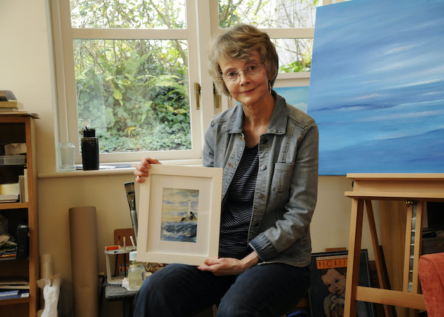 Sitting in an art studio, Kathleen Reardon displays a painting of a lighthouse