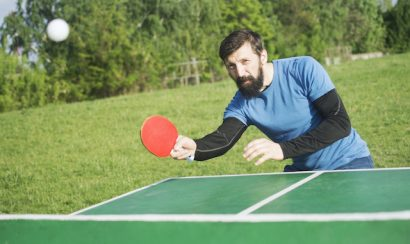 The bearded man is playing table tennis or pingpong outdoors as recreation.