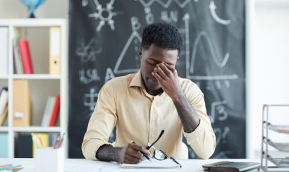 Tired young teacher sitting by desk in classroom and touching nose bridge