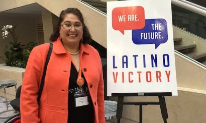 Maria De Leon standing in front of 'Latino Victory' poster