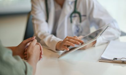 Shot of a doctor showing a patient some information on a digital tablet