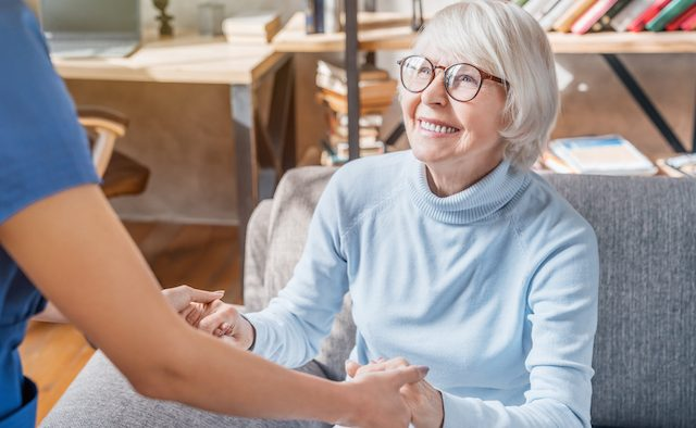 female professional caregiver taking care of elderly woman at home