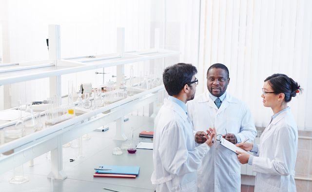 three scientists talking in laboratory