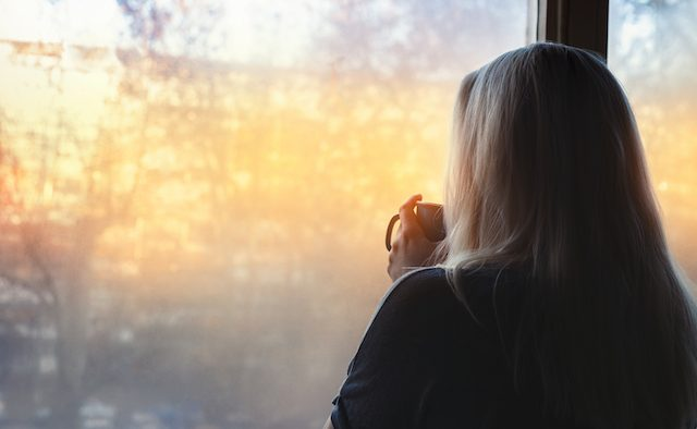 Blonde woman standing by the window, with coffee cup in hands, looking out into the morning light