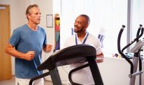 Man running on treadmill in medical setting.