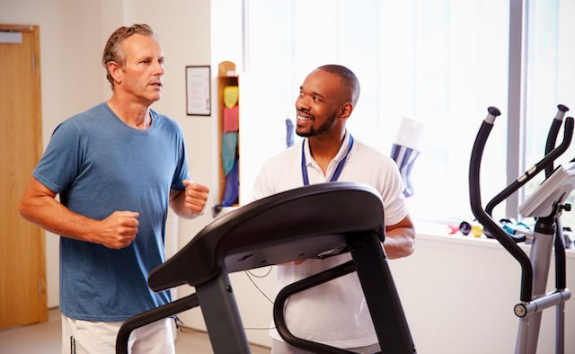 Man running on treadmill in medical setting.