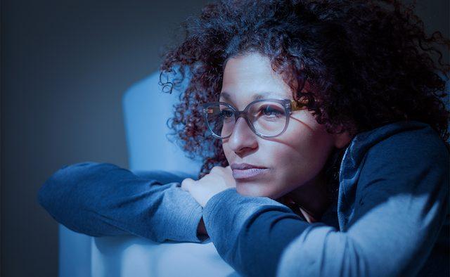 Woman lying on sofa at night.