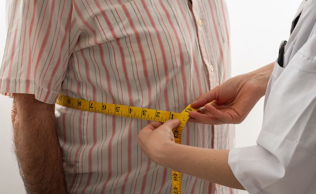 female doctor is measuring senior man's body circumference
