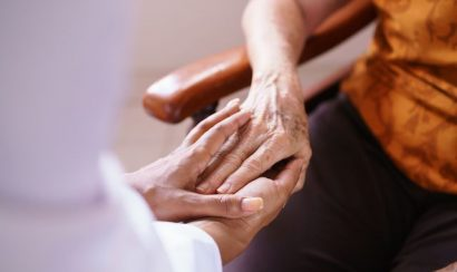 Closeup of a physician holding an older person's hand