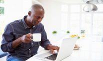 A man sits at a computer holding a mug