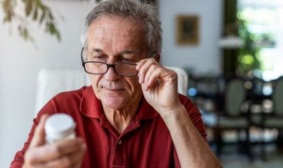 A man wearing glasses examines a pill bottle