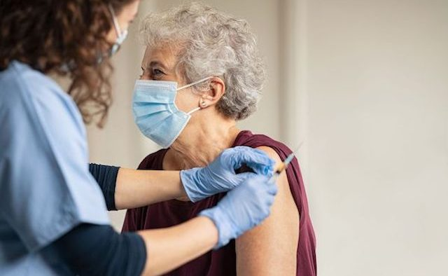 An older woman receives a vaccine
