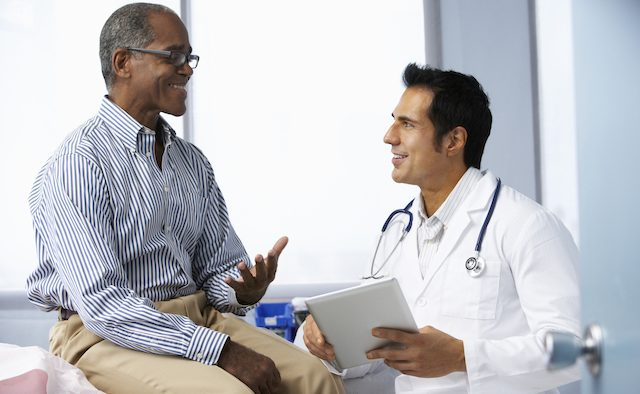 A male patient consults a clinician in a doctor's office