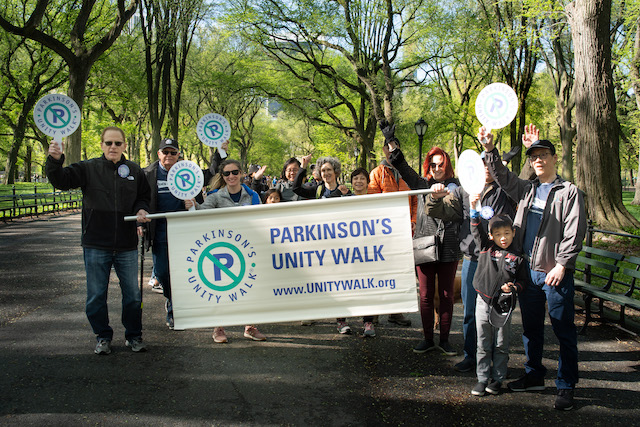 A large group holds a Parkinson's Unity Walk banner and signs in Central Park, New York City, US