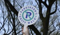 A Parkinson's Unity Walk sign is held up by someone off-frame
