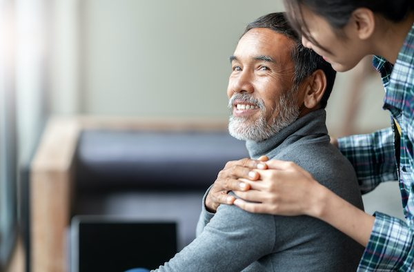 A young woman touches an older man's shoulder as he looks back at her