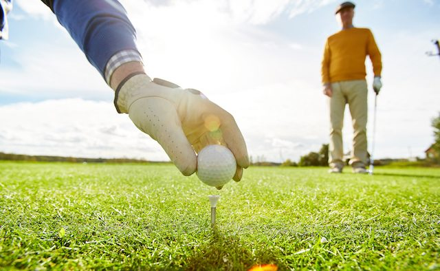 One of golf players putting ball on tee while the other one standing on background