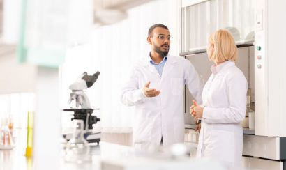 Two doctors in white coats converse in a lab
