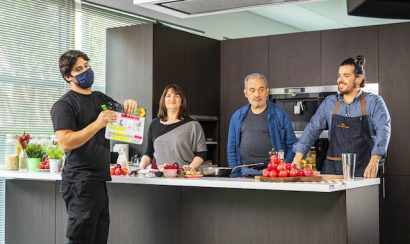 Four people stand at a kitchen counter filled with ingredients.
