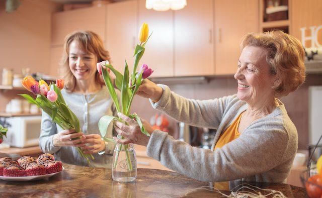 Two women arrange tulips in a vase
