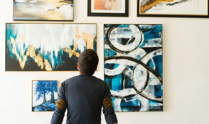 A person looks at a wall of paintings