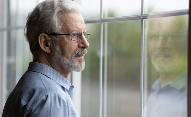 A middle-aged man wearing glasses looks out a window.