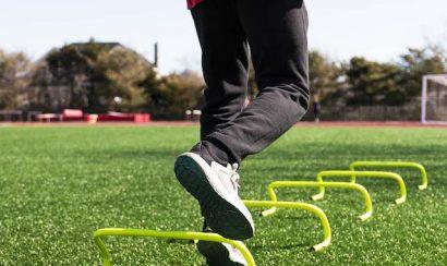 Man stepping over yellow mini banana hurdles on a field