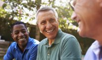 A closeup of three men smiling together outdoors
