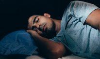 A man sleeps in a dark room.