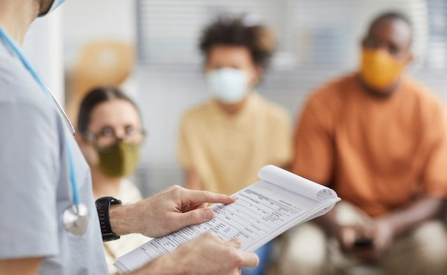 A clinician stands with a clipboard in front of people wearing Covid-19 masks.