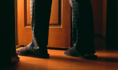 A man's legs are shown walking from a dark room.
