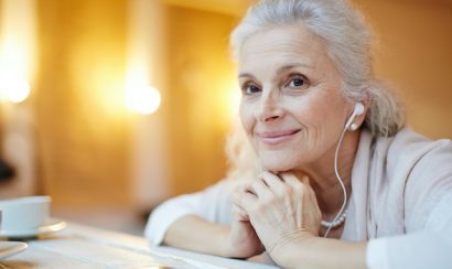 An older woman smiles to the distance with earphones on