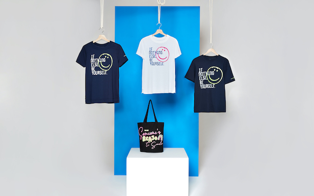 Three t-shirts and a tote bag are displayed against a blue backdrop.