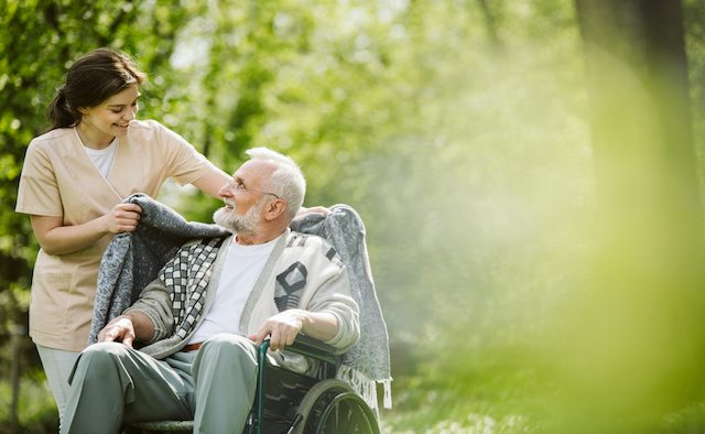 A health care worker and a man in a wheelchair smile at each other in the outdoors.