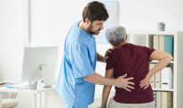 A clinician evaluates an older person's back pain in a doctor's office.