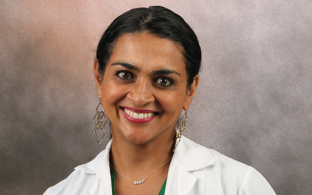 Dr Indu Subramanian smiles for a portrait in a lab coat.