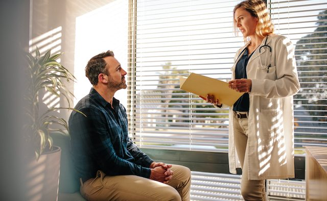 A clinician speaks to a patient in a sunny room.