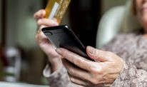 Old woman shopping online using a credit card and a smartphone at home