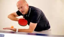 An action shot of Jense Greve playing table tennis.