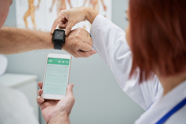 A clinician and patient consult a wearable tracking watch.