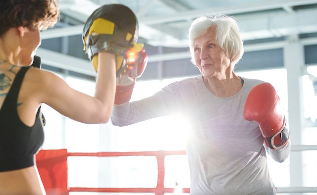 An older woman practices boxing with a trainer.