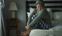 A woman sits with her knees up on the edge of her bed.
