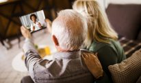 An older couple consult a clinician on a tablet.